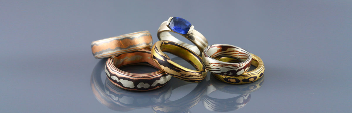 A collection of mokume gane rings featuring 18kt rose gold, 18k yellow gold, 18k white gold, palladium, silver and shakudo. Mokume gane plain rings can be used as wedding bands and mokume gane rings set with gemstones can be beautiful and unique engagement rings.