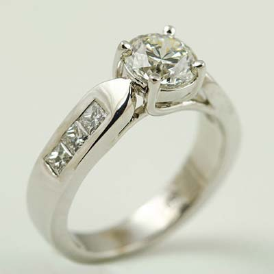 Centre round brilliant cut Diamond with princess cut diamonds in channel setting in the shoulders